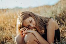 Girl Sitting On Yellow Grass Field