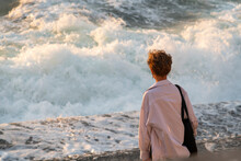 Rear View Of Caucasian Woman With Short Hair Hairstyle Standing On City Embankment And Looking At Large Waves Of Stormy Sea At Sunset. Selective Focus. Copy Space. The Theme Of Human And Nature.
