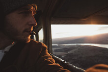 Man Inside Helicopter Looking Down River And Mountains During Sunset