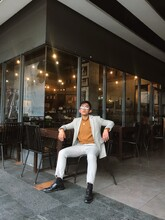 Man Sitting On Brown Chair Beside Shop Outdoor