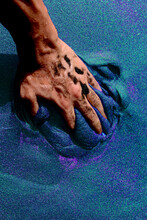 Persons Hand On Blue Sand