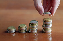 Person Stacking Coins On Increasingly Larger Stacks