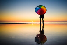 Silhouette Of Person Holding  Rainbow Umbrella Standing On Seashore During Sunset