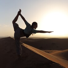 Silhouette Of Woman Doing Yoga Pose In Desert During Sunset
