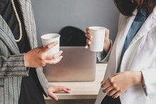 Two Businesswoman Having A Meeting And Drinking Coffee In The Office