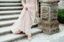 Woman In Pink Long Sleeve Dress And High Heels Walking On Gray Concrete Stairs