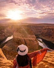 Woman Sitting Beside The Horseshoe Bend  In Glen Canyon National Recreation Area In Arizona,USA