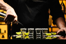 Bartender Pouring Tasty Tequila Into Glasses At Table In Bar