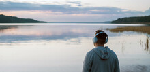 Balance Calmness And Harmony With Yourself. A Man Meditates With Headphones In Nature. He Listens To Pleasant, Calm Music.