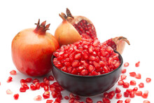 Close-up Of One Organic Red Pomegranate (Punica Granatum) And Red Pods(seed) In A Black Ceramic Bowl Isolated Over White Background.