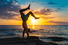 A Fit Young Man Practices Yoga Poses On The Beach During Sunset. Meditation And Concentration Posture On The Sea Side Of Relaxing Day At Dawn Surrounding By Nature.