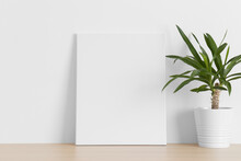 White Canvas Mockup With A Yucca Plant On The Wooden Table.