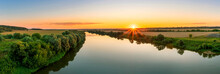 Scenic View From Above At Beautiful Summer River Sunset With Reflection On Water With Green Bushes, Golden Sun Rays, Calm Water ,deep Blue Sky And Glow On A Background, Evening Landscape