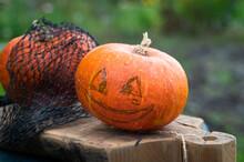Halloween Scary Pumpkin With A Smile In Autumn Garden. Preparation For Celebration. Preparing Pumpkin For Halloween. Jack-O-Lantern. Making Pumpkin Decor For Halloween.
