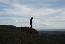 A Hooded Figure Walking Towards The Top Of A Rocky Outcrop. Looking Down Across The Landscape