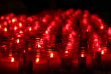 Rows Of Glowing Red Candles In The Dark