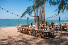 Celebration Venue With Wooden Long Table, Chair, Light Bulb Hanging And Plant Decoration In Retro Style On The Beach