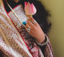 Close-up Shot Of A Woman With Sari And Holding Lotus Flower
