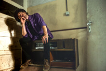Man In Purple Shirt And Black Pants Sitting On An Old Record Player