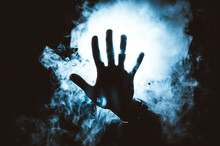 Persons 's Hand In Front Of Blue Light And Smoke