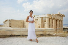 Woman In Long White Dress Standing Near Ancient Ruins In Athena, Greece