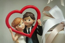 Two Statuettes Of Newlyweds In Love, Standing In A Porcelain Heart