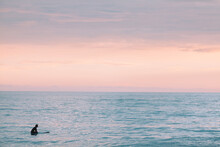 Lone Surfer At Sunset In The Calm Ocean.