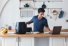Happy Young Man Standing At Kitchen Table And Cooking Toast Bread By Air Fryer Machine, Watching Culinary TV Show Online On Laptop. New Normal Work Lifestyle At Home. Technology Smart Cooking Device.