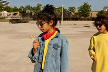 Cool Girl Eating A Lollipop With Her Friend Outdoor