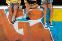 Children's Legs Hanging On A Wall With Graffiti