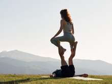 Woman And Man Doing Straddle Throne Pose In Mountains