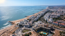 Beautiful Aerial Cityscapes Of The Tourist Portuguese City Of Quarteira. On The Seashore During The Beach Season With Tourists Who Are Sunbathing.