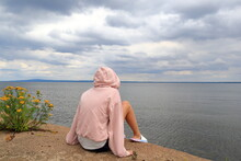Female In A Pink Hood Sweater Looking Out Over The Water. Sitting Next To The Flower Tansy. Part Of The Swedish Lake Called Vänern Or Vanern. Lidköping, Sweden, Europe.