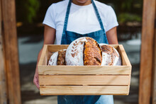 Woman Holds Fresh Made Sourdough Bread In A Wood Crate.
