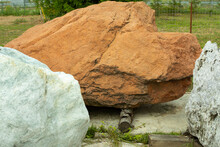 Red Stone. Big Cobblestone. A Piece Of Rock To Install In The Garden. Park Landscape. A Large Rock Lies On The Street.