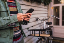Crop Man Using Smartphone Near Vintage Bicycle Parked In A Wooden Wall With Bushes In City