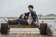 Asian Man Sitting On A Bench With His Feet Up