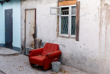 An Old Red Armchair Outside A House