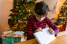Boy Opening Christmas Gift At Table
