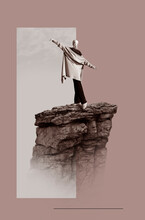 Woman Standing With Arms Outstretched On Rock