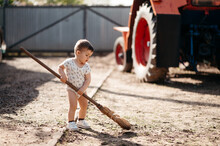 Toddler Sweeping Country Yard