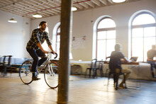 Casual Businessman Riding Bicycle In Open Office