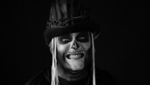Creepy Man With Skeleton Makeup In Top-hat With Feathers. Guy Making Faces, Trying To Scare, Toothy Smile. Voodoo Rituals. Baron Saturday. Halloween Thematic Party. Black Background. Black And White