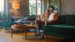 Leinwandbild Motiv Couple Watches TV together while Sitting on a Couch in the Living Room. Girlfriend and Boyfriend embrace, cuddle, talk, smile and watch Television Streaming Services. Home with Cozy Stylish Interior.
