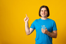 Young Man Using Smartphone Standing Over Isolated Yellow Background Very Happy Pointing With Hand And Finger To The Side.