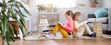Two Children Sitting On The Floor In The Room And Reading Books