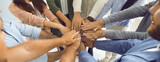 Team of business people who work together joining hands. Teamwork themed banner background with group of colleagues standing in circle and stacking hands. Concept of union, teamwork and partnership