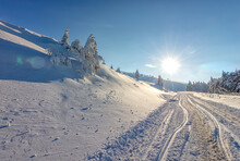 Sun, Snow And Car Tracks On The Road In The Winter In The Mountain. The Concept Of Winter Travel By Car.