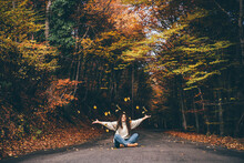 Positive Curly Haired Woman In Sweater Throwing Dry Leaves In Picturesque Autumn Forest With Colorful Trees On Sunny Day.