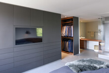 Spacious Bedroom With A Big Black Dresser And A Television